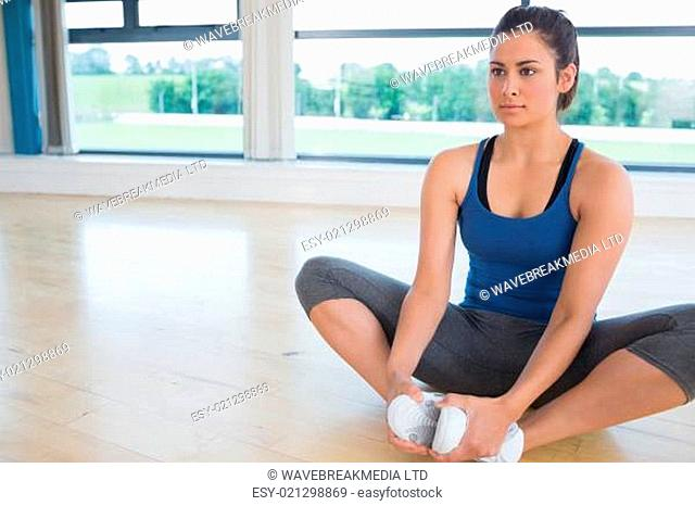 Woman doing bound angle yoga pose in fitness studio