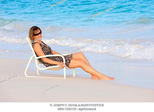 Woman enjoys beach chair on the sand, Bermuda Island, Atlantic Ocean