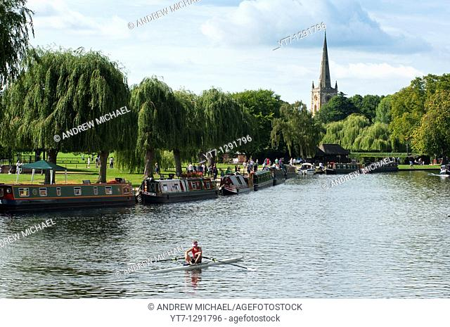 A scenic shot of the river and he Holy Trinity Church as a rower goes past  Stratford upon Avon, England
