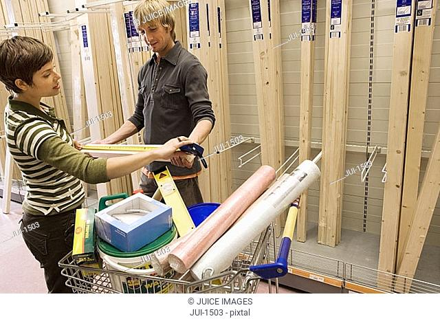 Couple shopping in DIY store, woman measuring piece of wood with tape measure