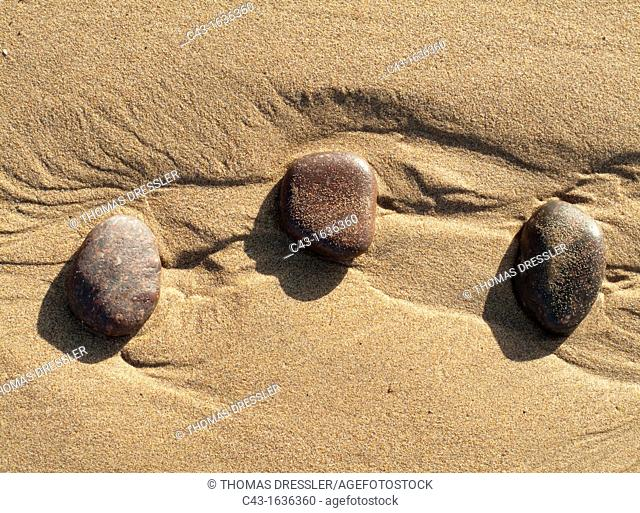 Morocco - Pebbles in the sand at Legzira beach at the shore of the Atlantic Ocean, north of the town of Sidi Ifni in southwest Morocco