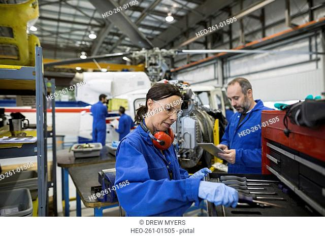 Helicopter mechanics at toolbox in airplane hangar