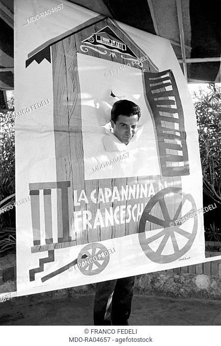 French musician Gilbert Becaud (François Gilbert Silly) posing with the poster of his show. Italy, 1960