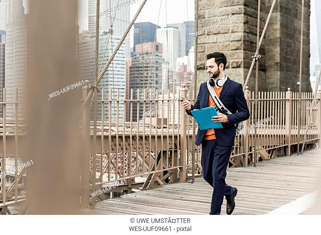 USA, New York City, man walking on Brooklyn Bridge using cell phone