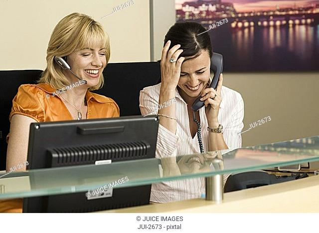 Two receptionists working at reception desk, woman holding phone receiver, second woman with headset
