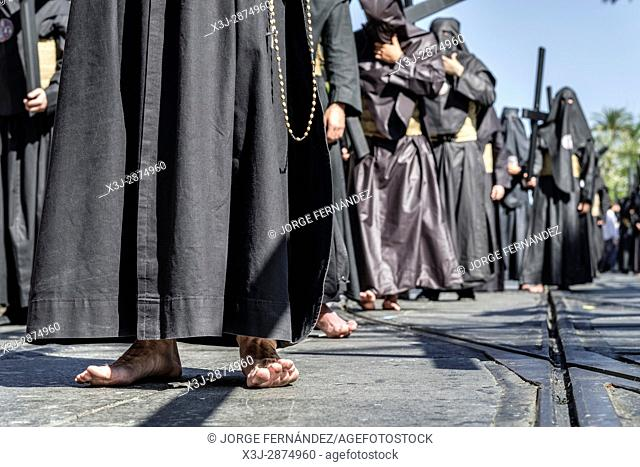 Penitents march barefoot along with the procession carrying a cross in order to keep a promise or fulfill a penance