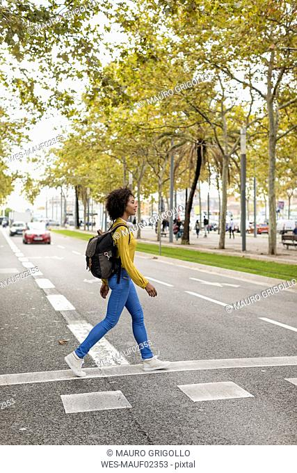 Woman with backpack crossing the street