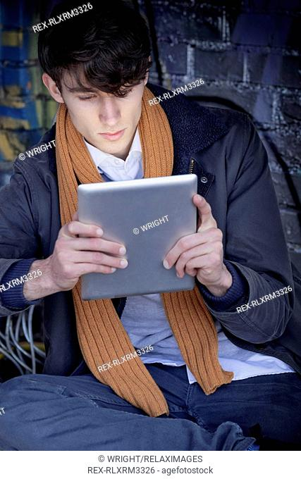 Portrait young man with tablet computer sitting