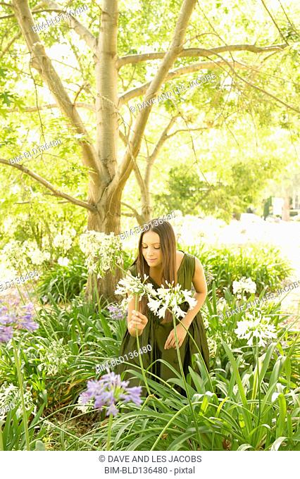 Mixed race woman smelling flowers outdoors