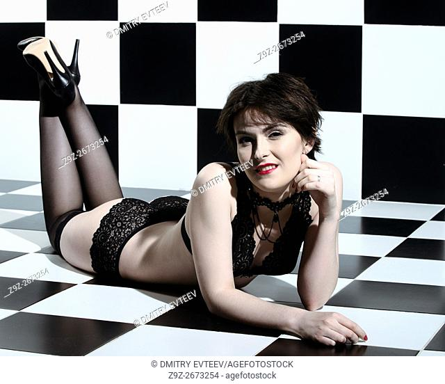 Shorthair woman portrait in black lace lingerie on chess background