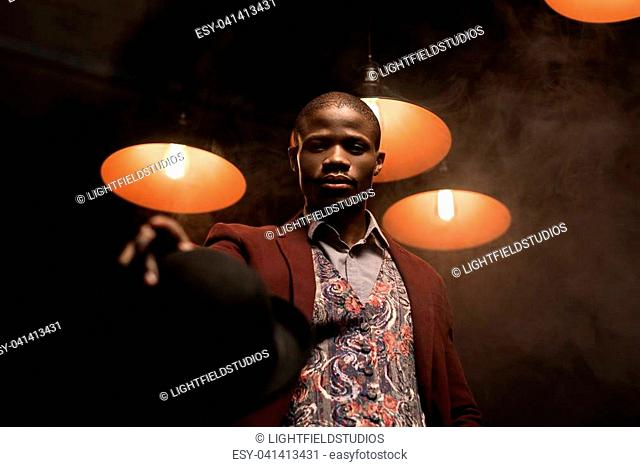 handsome fashionable african american man with hat in dark room with lamps