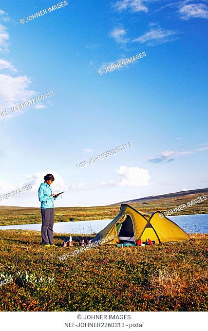 Woman camping at lake