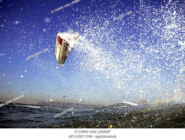 Jet ski pilot takes off from water in a fountain of spray