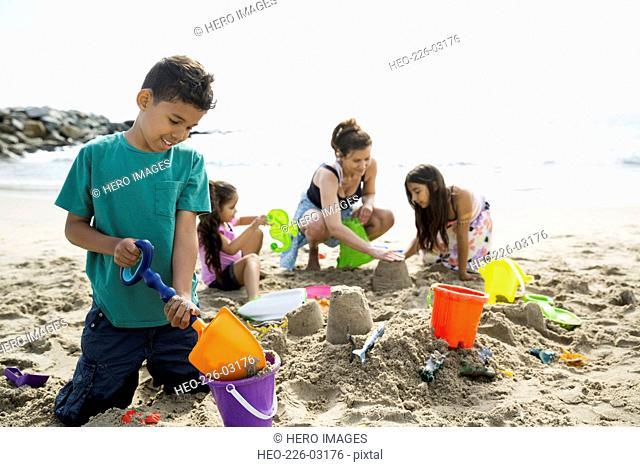 Family making sandcastle on sunny beach