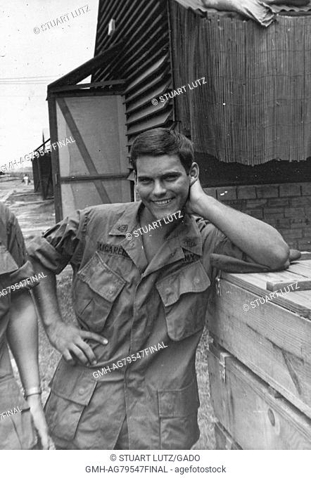 A United States Army serviceman posing with one hand on his hip and leaning his opposite elbow on a stack of crates, he is smiling gleefully for the...