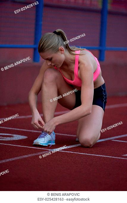 young runner sporty woman relaxing and stretching on athletic race track
