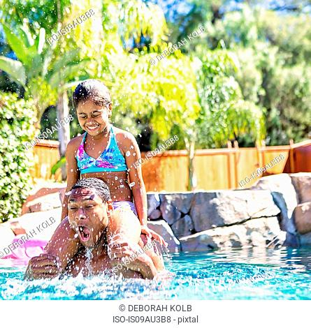 Daughter sitting on fathers shoulders in swimming pool, eyes closed splashing