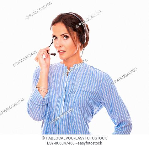 Portrait of charming female operator speaking with earphone while smiling at you on isolated studio