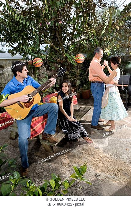A Mexican-American family playing music and dancing in the backyard of their house