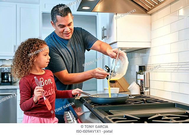Father helping daughter cook omelette on hob in kitchen, pouring egg into frying pan