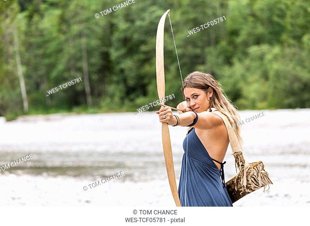 Archeress aiming with a bow in the nature