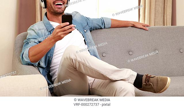 Handsome man listening to music and using smartphone