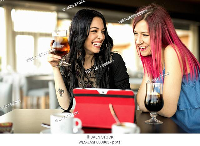 Young women in cafe using digital tablet, having a drink