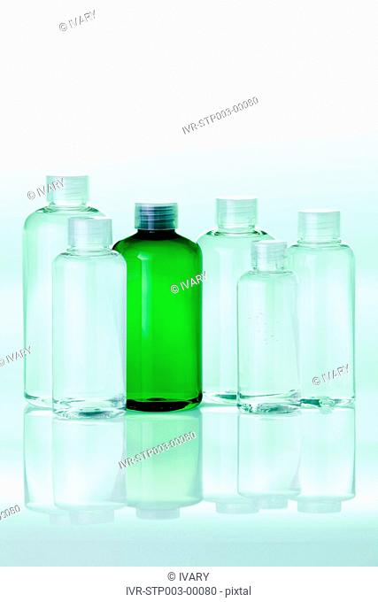 Transparent Bottles With Green Background And Reflection