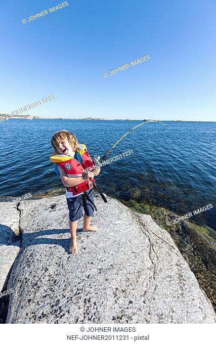 Happy boy fishing in sea