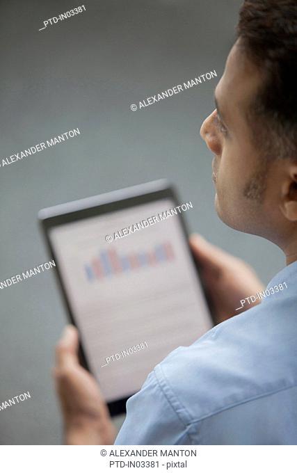 Singapore, Businessman holding digital tablet