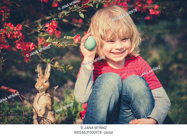 Boy in garden holding Easter egg