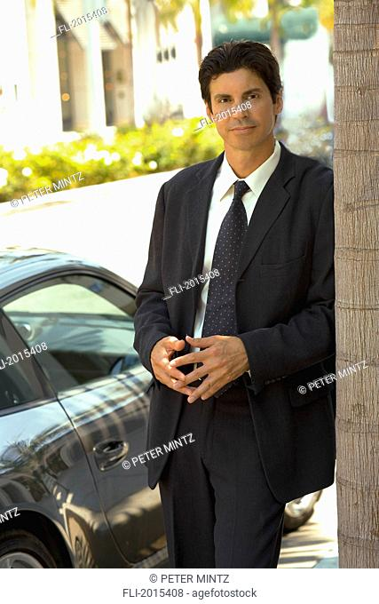 Businessman Leaning Against Tree