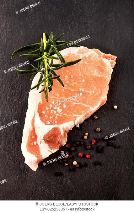 raw pork loin steak with rosemary, peppercorn and coarse salt on slate
