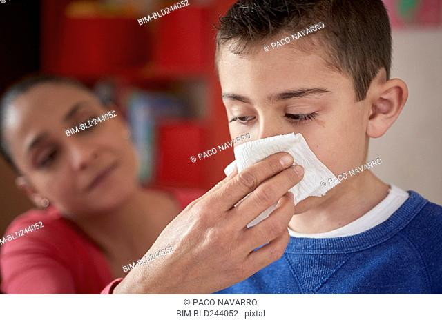 Hispanic mother wiping nose of son with tissue