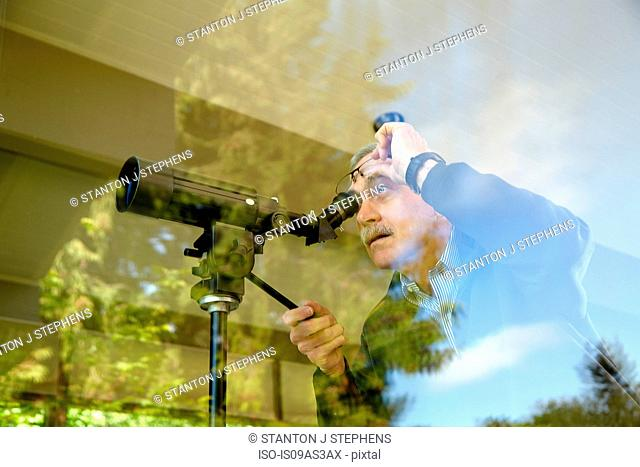 Senior man at home, using telescope through window
