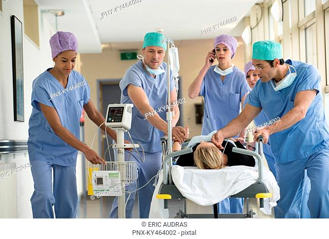 Medical professionals pushing patient on gurney in a hospital