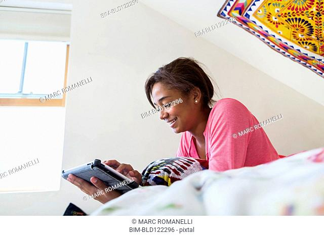 Mixed race teenage girl using digital tablet on bed