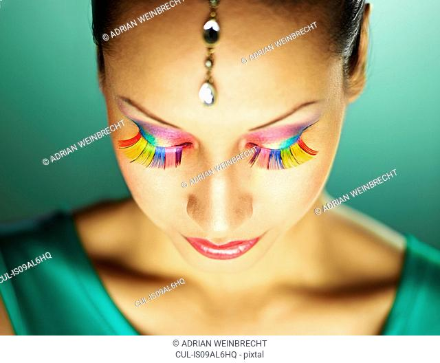 Young woman with jewel head accessory and coloured eyelashes