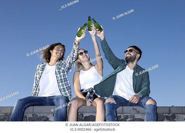 Cheerful men and woman friends sitting together and clinking bottles of beer. Lanzarote, Canary Islands, Spain