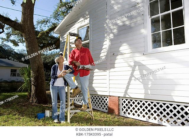 Mature couple with ladder and painting tools preparing to paint outside of house