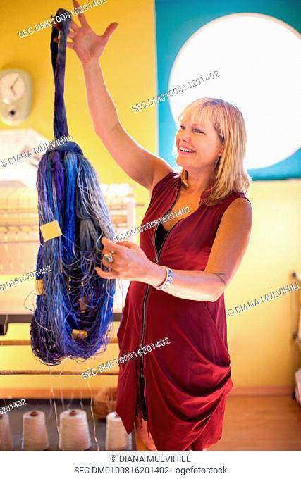 Woman looking at dried yarn