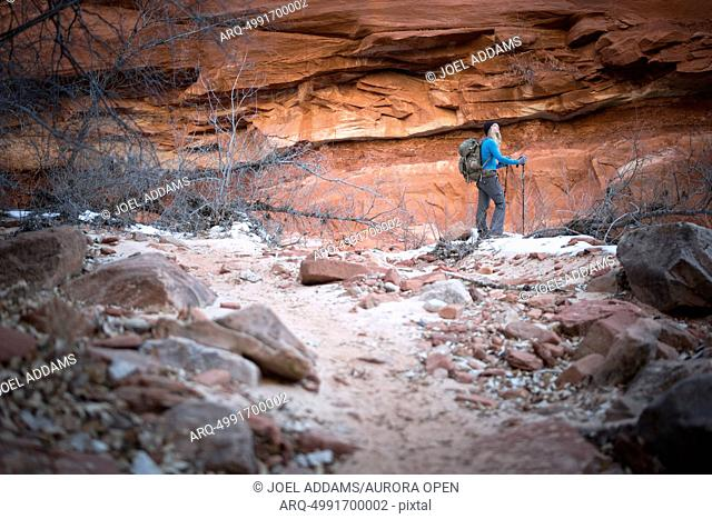 A young woman hikes the red rock of Zion National Park