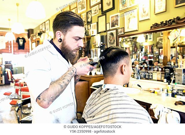 Rotterdam, Netherlands. Barber store Schorem. Barber helping his customer in his barber shop by cutting and modeling his hair