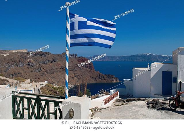 Flag flying from top of isolated village of Thirassia across from Santorini Greece in Greek Islands