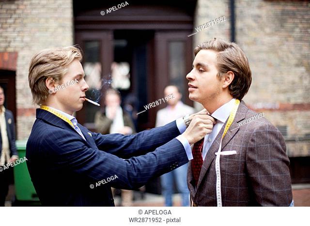 Handsome owner adjusting partner's necktie while smoking cigarette against building
