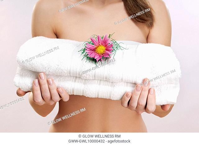 Mid section view of a woman holding towels with a flower