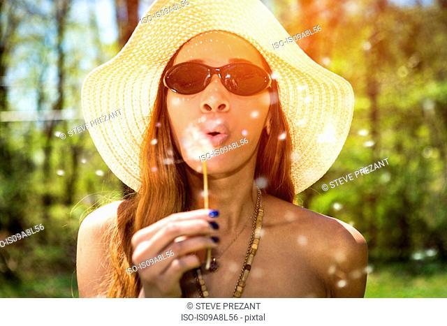 Woman blowing dandelion clock