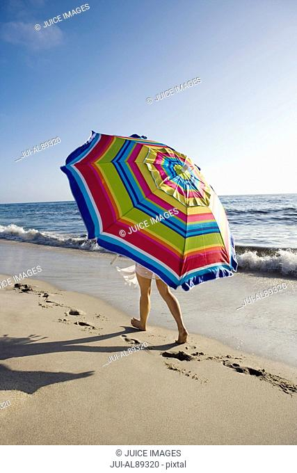 Person walking under umbrella at beach