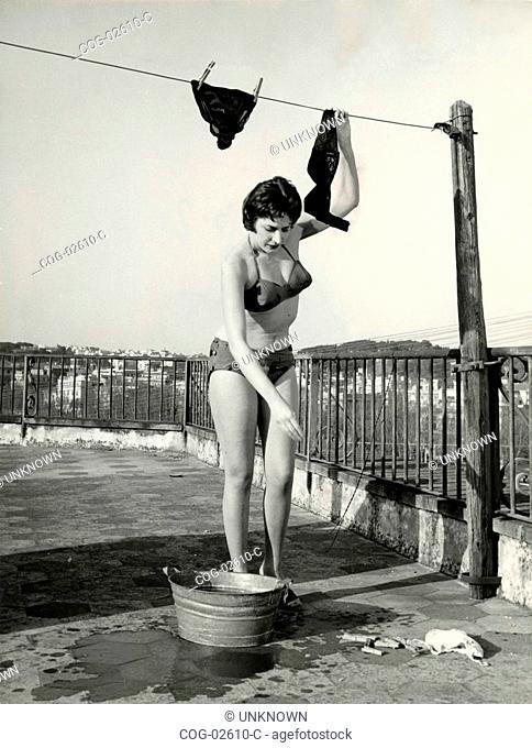 Italian actress Bianca Fusari hanging laundry in her underwear and bra, Italy