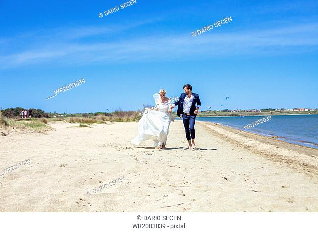 Bride and bridegroom running on beach